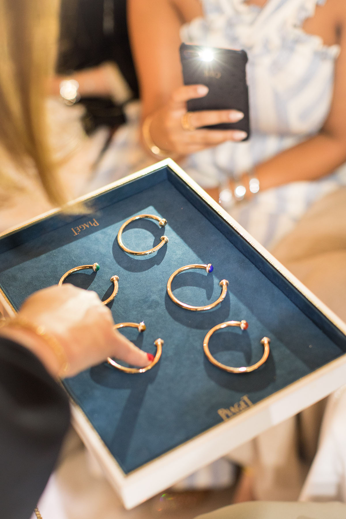 Sales lady showcasing 5 new bracelets at the Piaget event by Loesje Kessels Fashion Photographer Dubai